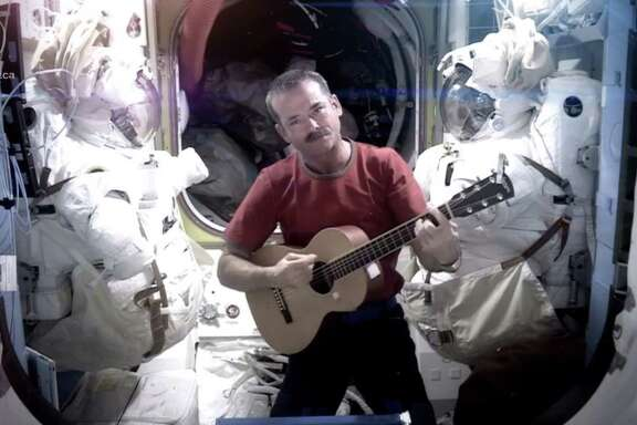 "Astronaut Chris Hadfield wields a guitar while recording the first music video from space on Sunday, a  cover version of David Bowie's ""Space Oddity."""