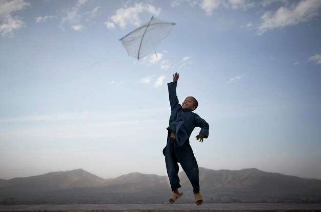 An Afghan boy flies his kite on a hill overlooking Kabul, Afghanistan, May 13, 2013. Banned during the Taliban regime, kite flying is once again the main recreational escape for Afghan boys and some men. Photo: Anja Niedringhaus, Associated Press / AP