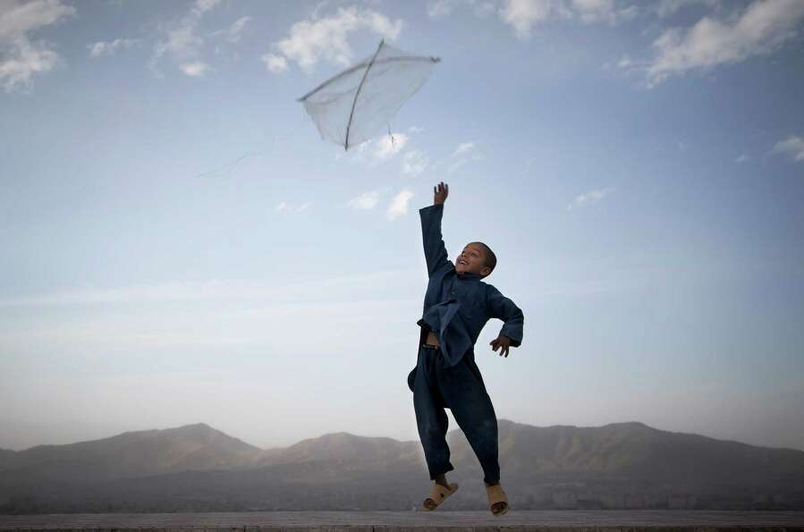 An Afghan boy flies his kite on a hill overlooking Kabul, Afghanistan, May 13, 2013. Banned during t
