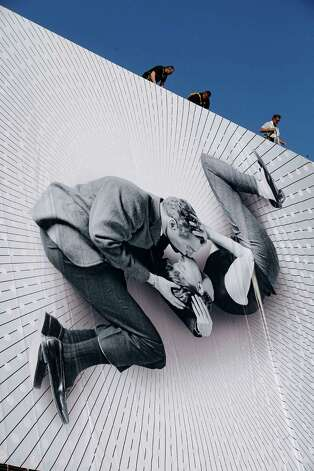 Workers set up a giant 66th Cannes Film Festival official poster at the Cannes Festival Palace, Monday, May 13, 2013. The poster shows Paul Newman and Joanne Woodward kissing, on the set of the film 'A New Kind of Love ',  directed by Melville Shavelson in 1963. The Cannes Film Festival will start on Wednesday, May 15. Photo: Lionel Cironneau, Associated Press / AP