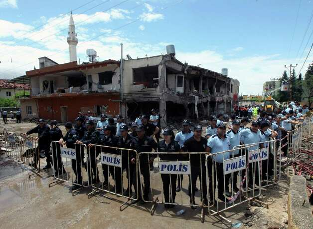 "Turkish riot police surround the destroyed shops two days after the explosions on Saturday that killed 46 and injured about 50 others, in Reyhanli, near Turkey's border with Syria, Monday, May 13, 2013. Prime Minister Recep Tayyip Erdogan said Monday Turkey would ""not refrain"" from responding to twin car bombings it has blamed on Syria but also said it would also act with caution and not be drawn into its neighbor's civil war. Photo: Burhan Ozbilici, Associated Press / AP"
