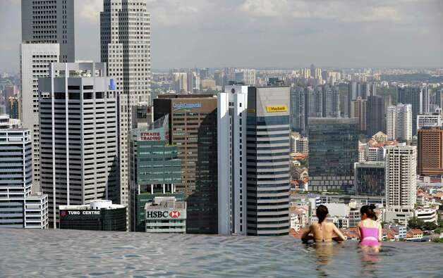 Guests of the Marina Bay Sands hotel in Singapore look over the city-state's financial district from a rooftop swimming pool on May 13, 2013. Singapore's trade-driven economy shrank in the first quarter as demand for exports remained weak, but a robust construction sector cushioned the decline, preliminary government estimates showed on April 12. Photo: ROSLAN RAHMAN, AFP/Getty Images / AFP