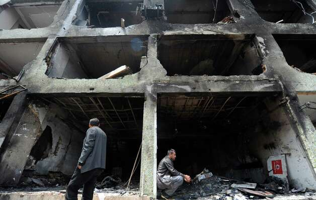 People wander around a damaged building on May 13, 2013 at Reyhanli in Hatay, just a few kilometres from the main border crossing into Syria. Turkey recovered on May 13 the bodies of two more people killed in the twin bombings near the Syrian border town , pushing up the death toll to 48 as many others remained missing. The bodies were found in a sewer near the blast zones in the southeastern border town two days after twin car bombings which Ankara blamed on a radical Marxist group affiliated with the Damascus regime. Photo: BULENT KILIC, AFP/Getty Images / AFP