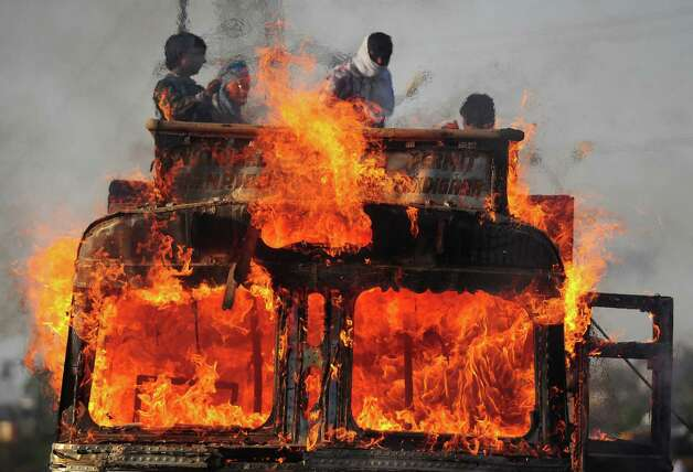 Indian labourers stand on top of a grain transport truck that caught fire after an oil leak leakage in Allahabad on May 13, 2013.   Bad roads, speeding vehicles and poor driving are among the contributing factors to road accidents.  A total of 131,834 people died in road accidents in India in 2011, according to the government's National Crime Records Bureau, which works out at 15 an hour. Photo: SANJAY KANOJIA, AFP/Getty Images / AFP