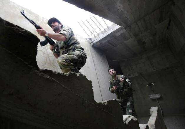 Syrian troops take control of the village of Western Dumayna, some seven kilometers north of the rebel-held city of Qusayr, on May 13, 2013. Syrian troops captured three villages in the strategic Qusayr area of Homs province, allowing them to cut supply lines to rebels inside Qusayr town, a military officer told AFP. Photo: JOSEPH EID, AFP/Getty Images / AFP