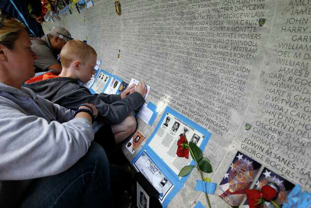 Aiden Szymanski, 9, make rubbing of his father's friend name, police officer Paul Hernandez of Texas, from the wall of fallen police officers at the National Law Enforcement Officers Memorial during the National Police Week in Washington, May 13,  2013. Photo: Jose Luis Magana, Associated Press / FR159526 AP