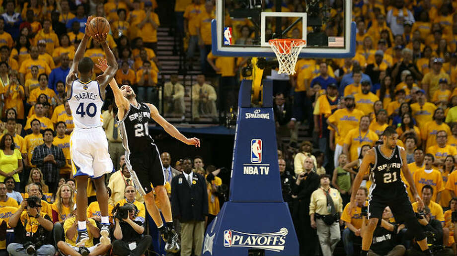 The Warriors' Harrison Barnes shoots over the Spurs' Manu Ginobili during Sunday's Game 4 in Oakland. Jed Jacobsohn / Getty Images