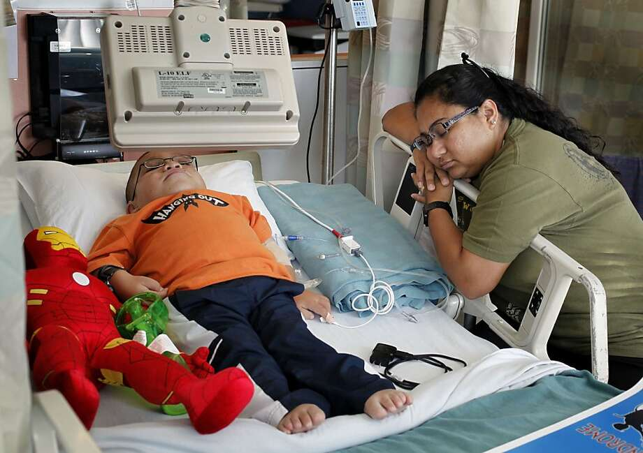 Juan Romero, a 13-year-old Mexican native from Los Angeles, receives his weekly infusion of medication to treat his Morquio A syndrome as his mother's partner, Liz Ramos, shuts her eyes for a moment at Children's Hospital Oakland. Photo: Michael Macor, The Chronicle