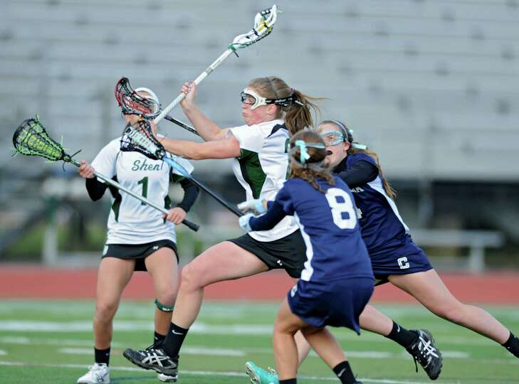 Shenendehowa senior attack Kelly Wall, center, takes a shot at the net and scores during a lacrosse