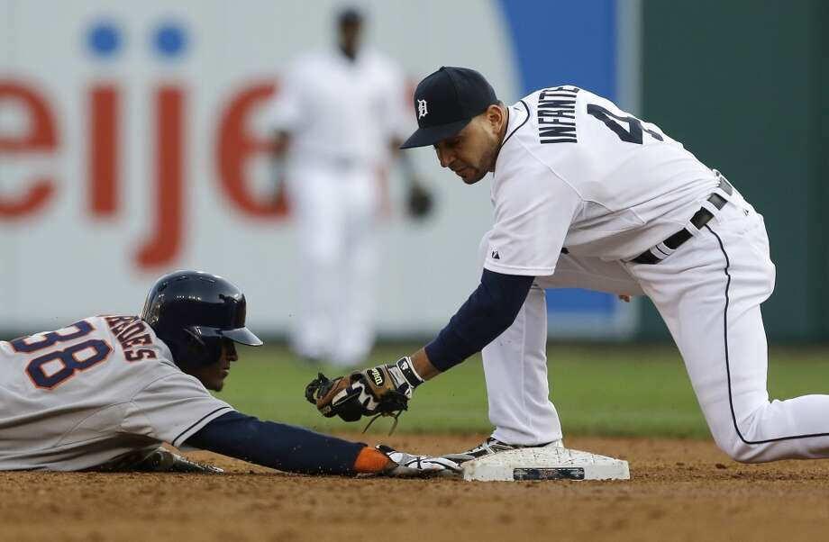 Jimmy Paredes of the Astros overshoots second on a steal but manages to beat the tag of Tigers second baseman Omar Infante during the third inning.