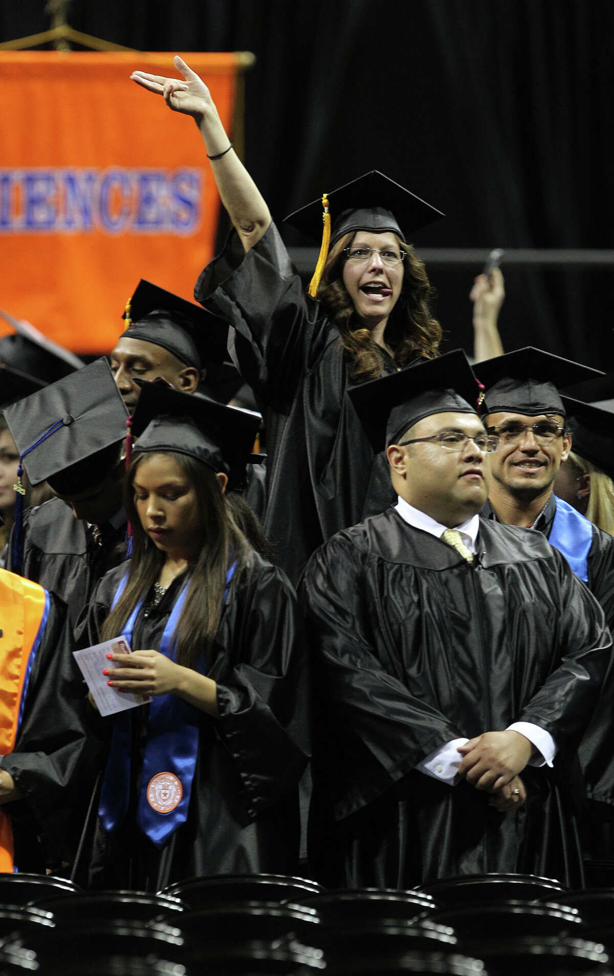 A student gets up high to catch the attention of family and friends during the first of two University of Texas at San Antonio graduation ceremonies at the Alamodome, Monday, May 13, 2013.