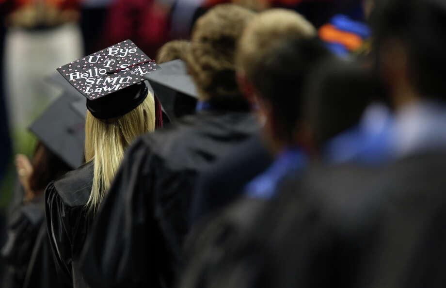 A student decorates her cap during the first of two University of Texas at San Antonio graduation ceremonies at the Alamodome, Monday, May 13, 2013. Photo: JERRY LARA, San Antonio Express-News / © 2013 San Antonio Express-News