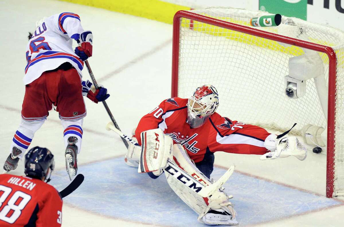 New York Rangers right wing Mats Zuccarello, left, from Norway, scores a goal against Washington Capitals goalie Braden Holtby (70) during the third period of Game 7 first-round NHL Stanley Cup playoff hockey series, Monday, May 13, 2013, in Washington. The Rangers won 5-0.