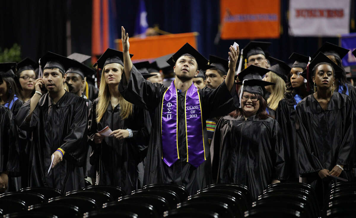 A member of the University of Texas at San Antonio Class of 2013 acknowledges the cheering crowd at the start of the first of two graduations at the Alamodome, Monday, May 13, 2013. Nearly 4,400 students graduated in the two ceremonies with over 40,000 family members and friends attending the first ever graduation at the Alamodome for the school.