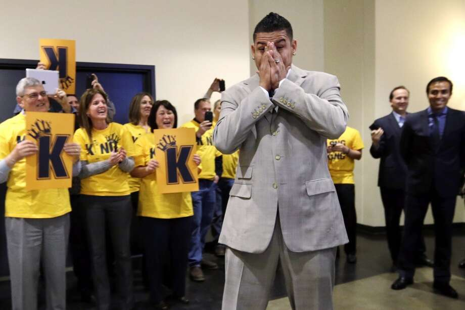 "Seattle Mariners' Felix Hernandez covers his face as he is greeted by front-office staff all wearing yellow ""Kings Court"" T-shirts before a news conference, Wednesday, Feb. 13, 2013, in Seattle. Hernandez signed a seven-year contract with the Mariners that makes him the highest-paid pitcher in baseball. The new deal will be worth $175 million."