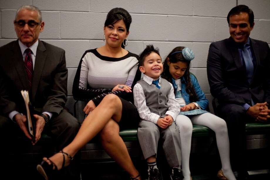 Sandra Hernandez watches her husband Felix Hernandez with their children, Jeremy, 3, and Mia, 7, as the Seattle Mariners pitcher signs a 7 year deal with the Mariners.