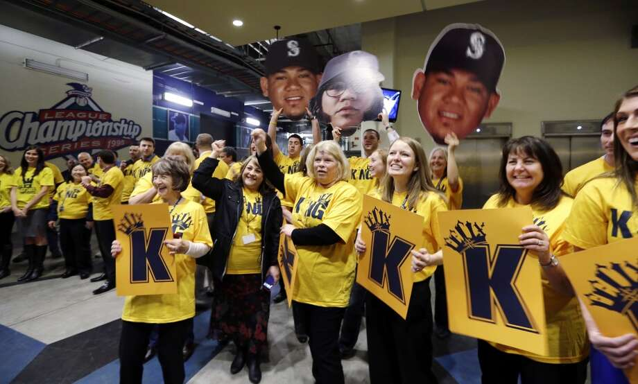 "Front-office staff hold signs and wear yellow ""Kings Court"" T-shirts as they greet Seattle Mariners' Felix Hernandez before a news conference, Wednesday, Feb. 13, 2013, in Seattle. Hernandez signed a seven-year contract with the Mariners that makes him the highest-paid pitcher in baseball. The new deal will be worth $175 million. (AP Photo/Elaine Thompson)"