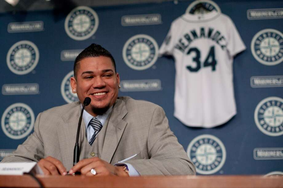 Seattle Mariner Felix Hernandez shares a light moment as he signs a 7 year deal with Mariners General Manger Jack Zduriencik on Wednesday, February 13, 2013 at Safeco Field in Seattle.