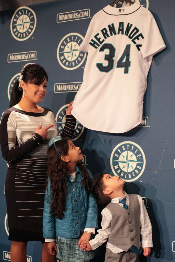 Sandra Hernandez points to her husband's jersey along with their children, Jeremy, 3, and Mia, 7, as Seattle Mariners pitcher Felix Hernandez signs a 7 year deal with Mariners General Manger Jack Zduriencik on Wednesday, February 13, 2013 at Safeco Field in Seattle.