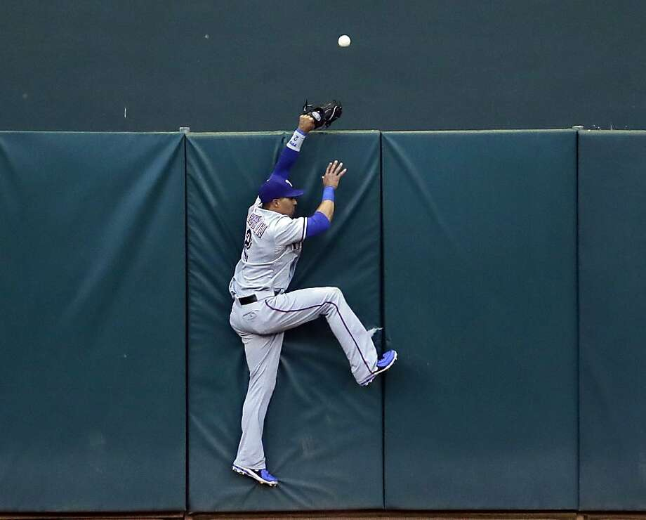 Texas Rangers center fielder Leonys Martin cannot catch a home run ball by Oakland Athletics' Yoenis Cespedes during the third inning of a baseball game on Monday, May 13, 2013 in Oakland. Calif. (AP Photo/Marcio Jose Sanchez) Photo: Marcio Jose Sanchez, Associated Press
