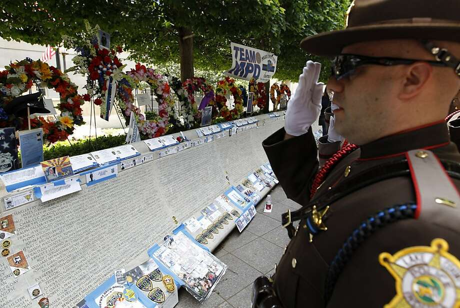 A Lake County, Indiana police officer salutes at the  National Law Enforcement Officers Memorial to the names of fallen police officers, Monday, May 13, 2013, at the memorial in Washington, during National Police Week. ( AP Photo/Jose Luis Magana) Photo: Jose Luis Magana, Associated Press