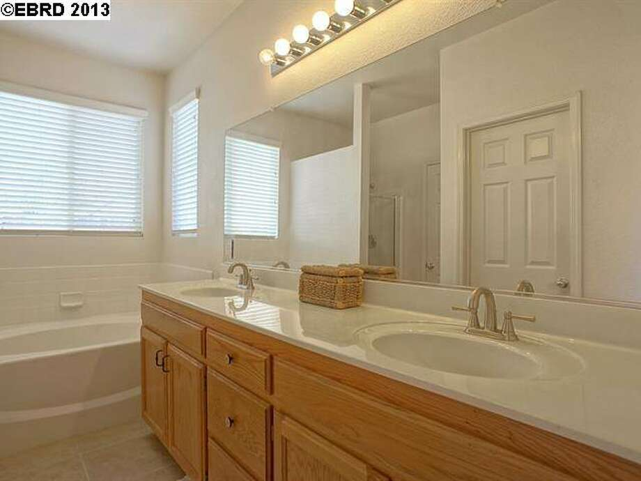 This shared bathroom has a shower over tub. The master bathroom features a stall shower.