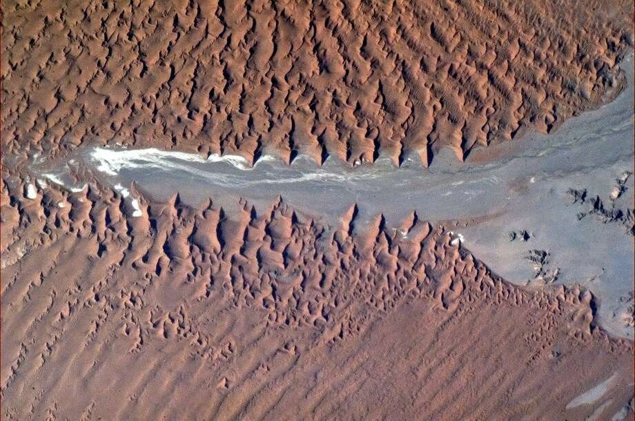 Frozen crests of sand break over the arid rock, Namibian coast, Africa. Photo: Col. Chris Hadfield/CSA/NASA