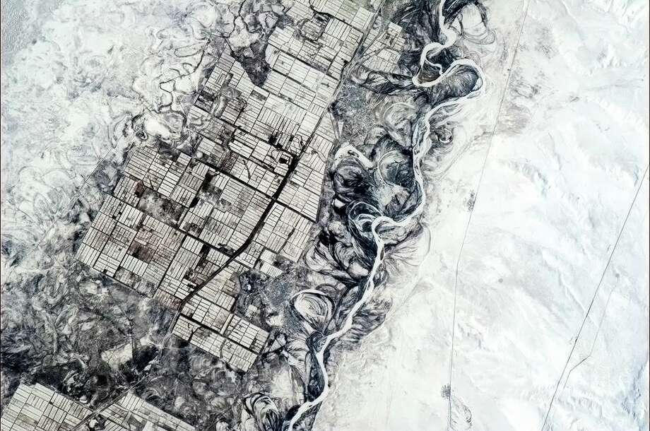Humans need straight lines, nature doesn't. Indecisive river and orderly farmers, central Asia. Photo: Col. Chris Hadfield/CSA/NASA