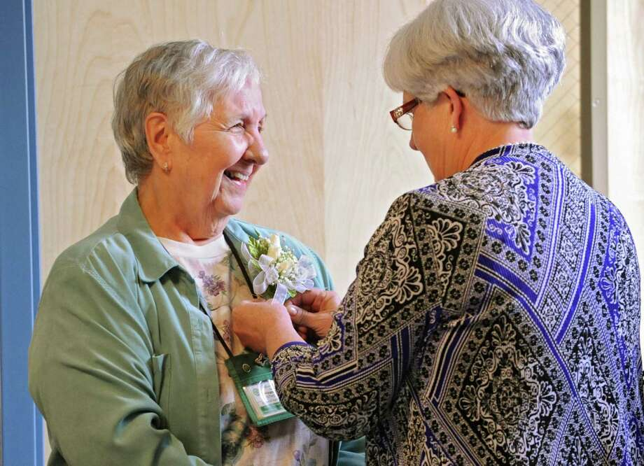 80-year-old nurse Esther Rappold has a corsage pinned to her shirt by Albany Memorial Hospital's head nurse Mary Hannan as she is recognized for 60 years of work at Albany Memorial Hospital on Monday, May 13, 2013 in Albany, N.Y. (Lori Van Buren / Times Union) Photo: Lori Van Buren / 00022369A