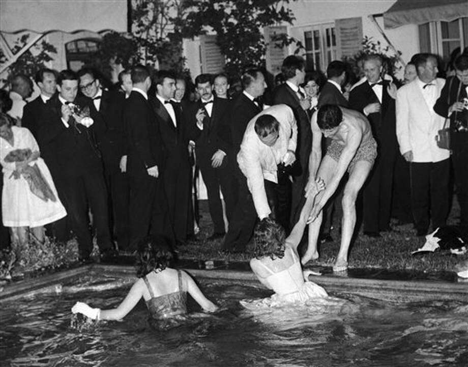 "Two unidentified starlets, still wearing their evening dresses, are helped from the floodlit swimming pool of a Cannes villa in France, rented by the French photographic agency Dalmas during a party on Tuesday, May 10, 1960 following the showing of ""La Dolce Vita"" at the Cannes film festival. Photo: ASSOCIATED PRESS / AP1960"