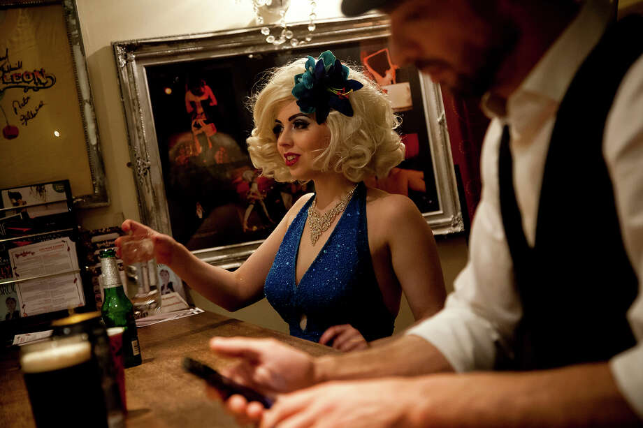 A burlesque performer stands at the bar during intermission at the London Burlesque Festival, May 11, 2013, in London, England. Now in its 7th year, Chaz Royal's London Burlesque Festival showcases some of the most eclectic and diverse acts in burlesque. The burlesque phenomenon that appeared in New York and London soon after the turn of the century has since proven to be more than just a retro revival, with no shortage of artists or fans. Photo: Warrick Page, Getty Images / 2013 Warrick Page