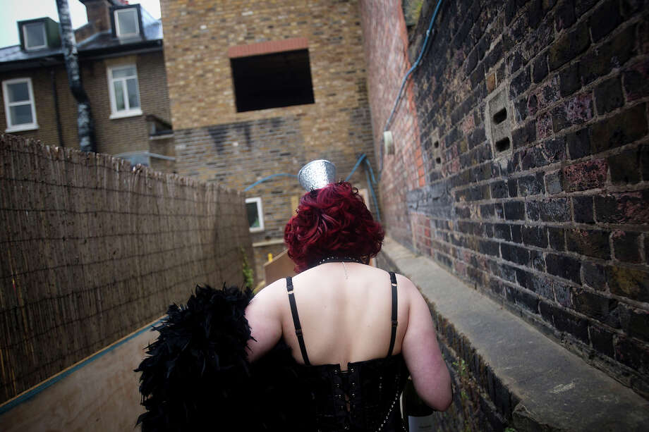 A burlesque performer walks between buildings backstage at the London Burlesque Festival, May 11, 2013, in London, England. Now in its 7th year, Chaz Royal's London Burlesque Festival showcases some of the most eclectic and diverse acts in burlesque. The burlesque phenomenon that appeared in New York and London soon after the turn of the century has since proven to be more than just a retro revival, with no shortage of artists or fans. Photo: Warrick Page, Getty Images / 2013 Warrick Page