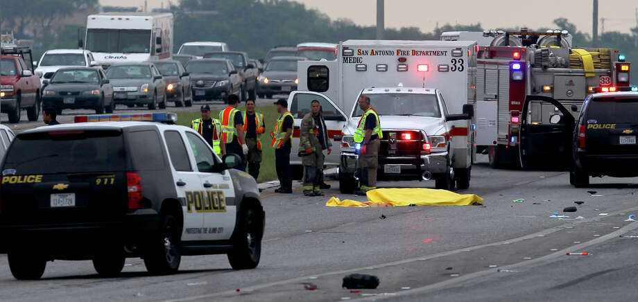 San Antonio police investigate at the scene of a fatal traffic accident that took place about 7:00 a.m. Tuesday May 14, 2013 at Highway 151 and Military Drive. Police said a 33-year-old woman was ejected from a Ford SUV when the vehicle rolled off the main lanes. The driver of the vehicle and a second passenger were not seriously hurt. The main lanes of 151 eastbound were blocked and diverted to the feeder road. Photo: JOHN DAVENPORT, SAN ANTONIO EXPRESS-NEWS / ©San Antonio Express-News/Photo may be sold to the public