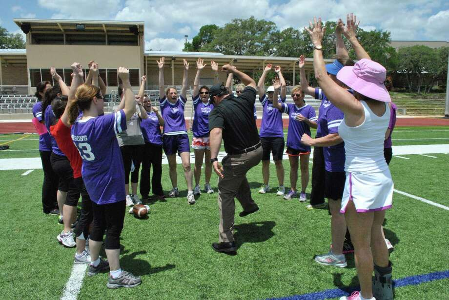 Saint Mary's Hall 'Gridiron Gals' get a pep talk from head varsity football coach David Beaudin as they prepare for the obstacle course challenge during a football clinic Saturday on campus. Photo: Courtesy Photo