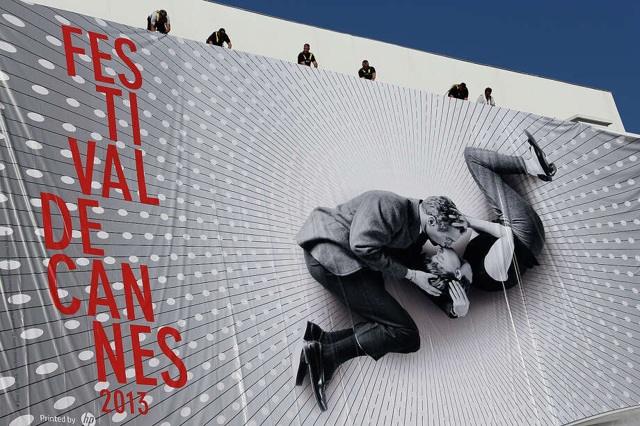 Workers set up a the giant official poster of the 66th Cannes Film Festival, featuring a 50-year-old photo of Hollywood love match Paul Newman and Joanne Woodward locked in a tender embrace, on May 13, 2013 on the facade of the palais des festivals in Cannes, southeastern France. Cannes, one of the world's top film festivals, opens on May 15 and will climax on May 26 with awards selected by a jury headed this year by Hollywood legend Steven Spielberg. Photo: VALERY HACHE, AFP/Getty Images / 2013 AFP