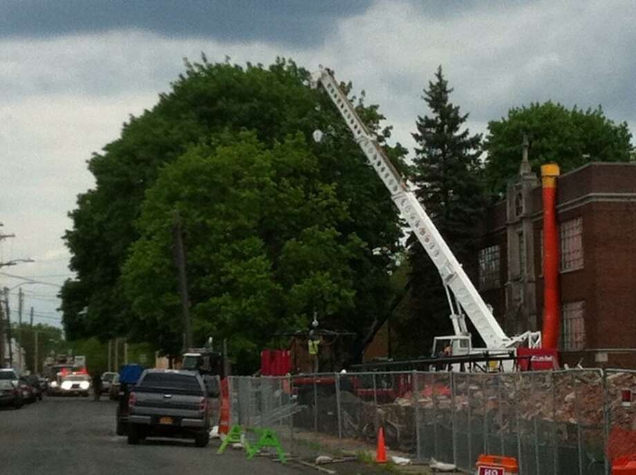 Workers prepare a crane for lifting part of larger crane that will be used to raze the St. Patrick's Church bell tower in Watervliet, N.Y., on Tuesday, May 14, 2013. (Kenneth C. Crowe / Times Union)