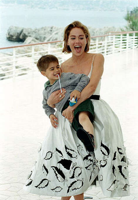 """American actress Sharon Stone, wearing a dress by Italian fashion designer Valentino, clowns around with an unidentified child who was passing by as she posed for photographers on the terrace of her hotel in Cap d'Antibes near Cannes, French Riviera, Friday, May 26, 1995.  Stone is in Cannes to promote her latest film, """"The Quick and the Dead."""" Photo: Remy De La Mauviniere, ASSOCIATED PRESS / AP1995"""