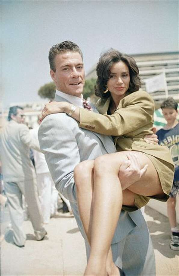 French actor Jean Claude Van Damme carries Gladys Portugues, on the beachfront of the Carlton Hotel in Cannes, French Riviera, May 8, 1992. The couple is in town for the 45th Cannes International Film Festival. Photo: Rhonda Birndorf, ASSOCIATED PRESS / AP1992