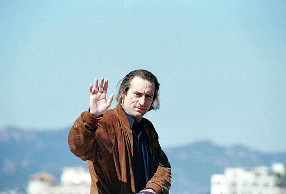 "American actor Robert De Niro waves to fans during the 44th Cannes Film Festival at the French Riviera, where he will present his motion picture ""Guilty by Suspicion,"" on May 17, 1991. Photo: Gilbert Tourte), ASSOCIATED PRESS / AP1991"