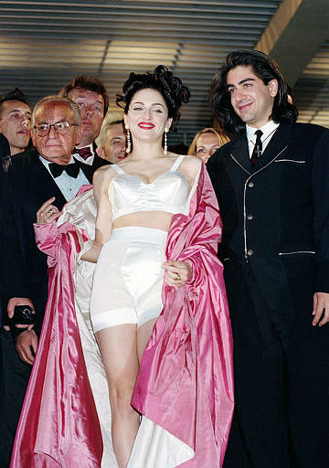 """American singer-actress Madonna leaves the screening of her movie """"In Bed with Madonna,"""" known as """"Truth or Dare"""" in the United States, with director Alek Keshishian, right, at the 44th Cannes Film Festival in France, May 14, 1991.  The documentary, filmed by the 26-year-old Harvard graduate, chronicles Madonna's 1990 """"Blond Ambition"""" tour. Photo: Gilbert Tourte, ASSOCIATED PRESS / AP1991"""
