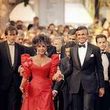American movie star Elizabeth Taylor, escorted by George Hamilton arrives at the Cannes Festival Palace in Cannes, France to attend the official gala for the Cannes Film Festival 40th Anniversary as seen in the Wednesday, May 13, 1987 photo.