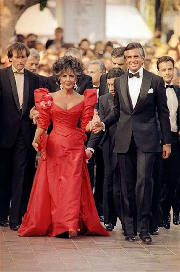 American movie star Elizabeth Taylor, escorted by George Hamilton arrives at the Cannes Festival Palace in Cannes, France to attend the official gala for the Cannes Film Festival 40th Anniversary as seen in the Wednesday, May 13, 1987 photo. Photo: Michael Lipchutz, ASSOCIATED PRESS / AP1987