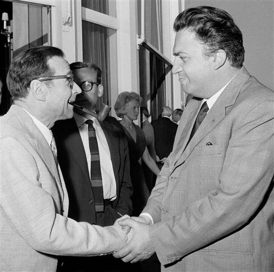 "Cannes Jury President, French detective novel author Georges Simenon, left, handshaking and congratulating Italian film director Federico Fellini, who has been awarded the ""Palme d'Or"" (Grand prix of the festival) for his film ""La Dolce Vita,"" May 20, 1960, Cannes, France. Photo: Wehrle, ASSOCIATED PRESS / AP1960"