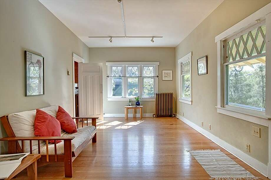 Living room of 1610 S. Hill St. The 1,960-square-foot Craftsman, built in 1912, has three bedrooms, 1.75 bathrooms, an office, a non-conforming basement apartment, a front porch and a patio on a 2,000-square-foot lot. It's listed for $299,950, although a sale is pending. Photo: Courtesy Jackie Leone Pleasant, Windermere Real Estate
