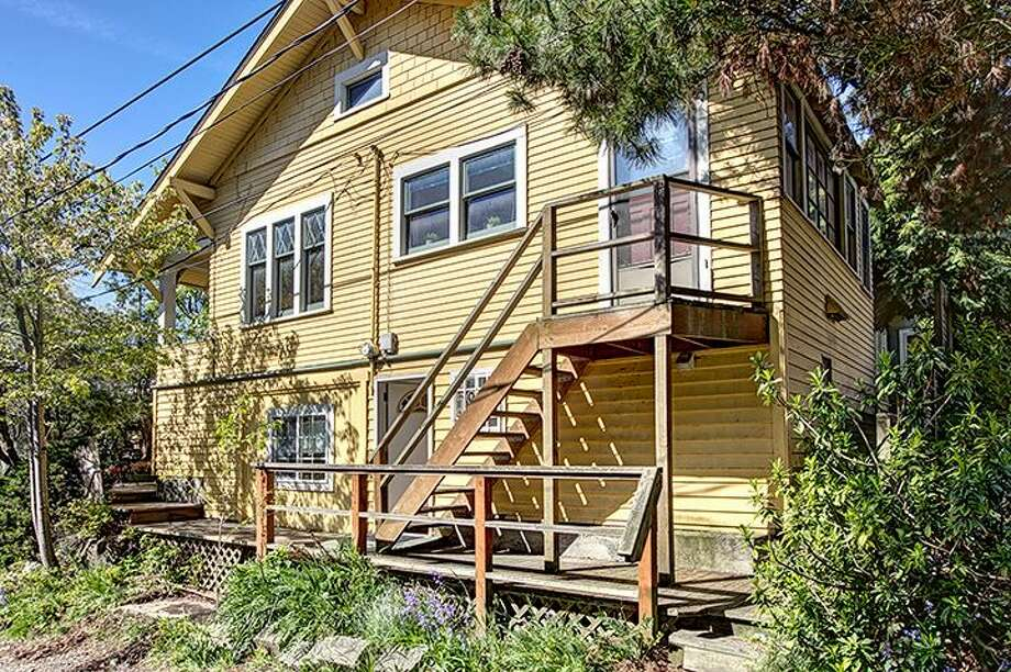 Side, with apartment entrance, of 1610 S. Hill St. The 1,960-square-foot Craftsman, built in 1912, has three bedrooms, 1.75 bathrooms, an office, a non-conforming basement apartment, a front porch and a patio on a 2,000-square-foot lot. It's listed for $299,950, although a sale is pending. Photo: Courtesy Jackie Leone Pleasant, Windermere Real Estate