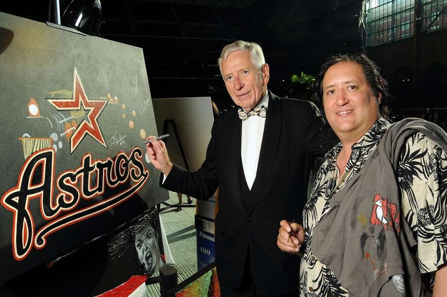 Drayton McLane signs a painting by artist Richard Nunez at the annual Astros Wives Gala at Minute Maid Park.