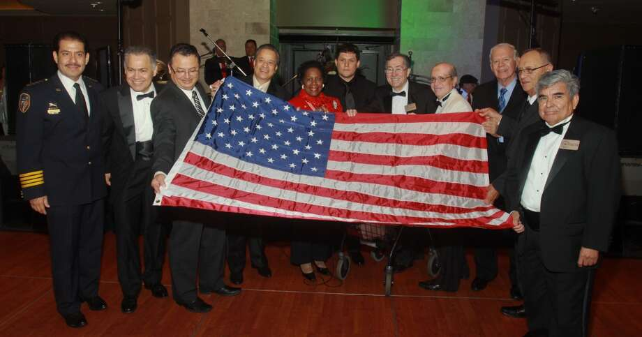 Congresswoman Sheila Jackson Lee, center, and a group of veterans, display the U.S. flag she presented at the Annual Latino Learning Center Night with the Stars Gala.