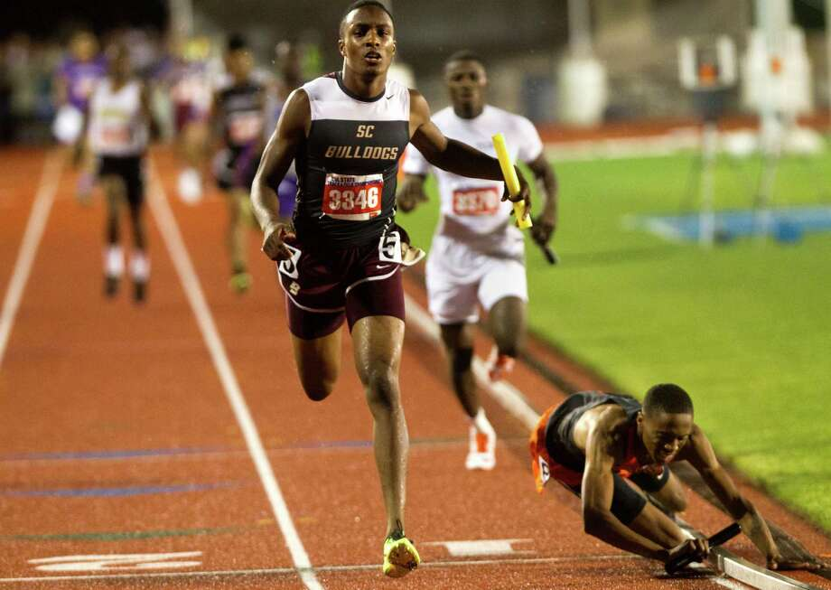 Lancaster's Eric Age, right, falls to the ground as Summer Creek's Aaron Sharp crosses the finish line to win the 4A Boys 4x400 meter relay during the UIL State Track and Field Championships in Austin. Photo: Cody Duty, Staff / © 2013 Houston Chronicle