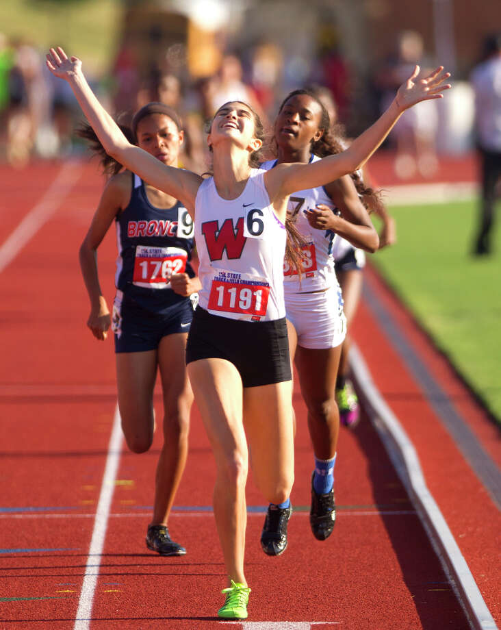 The Woodlands' Katie Willard raises her arms as she wins the 5A girls 800 meter race at the University Interscholastic League State Track and Field Championships in Austin. Photo: Cody Duty, Staff / © 2013 Houston Chronicle