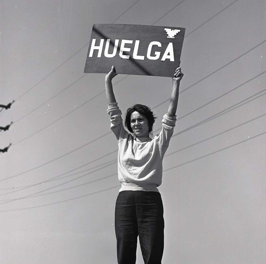 """Labor leader Dolores Huerta holds 'HUELGA' sign (""""Strike"""") above her head. Delano, California, September 24, 1965."""